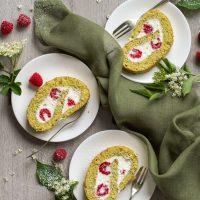 Biskuitrolle mit Himbeeren, Holunderblüten und Kürbiskernen